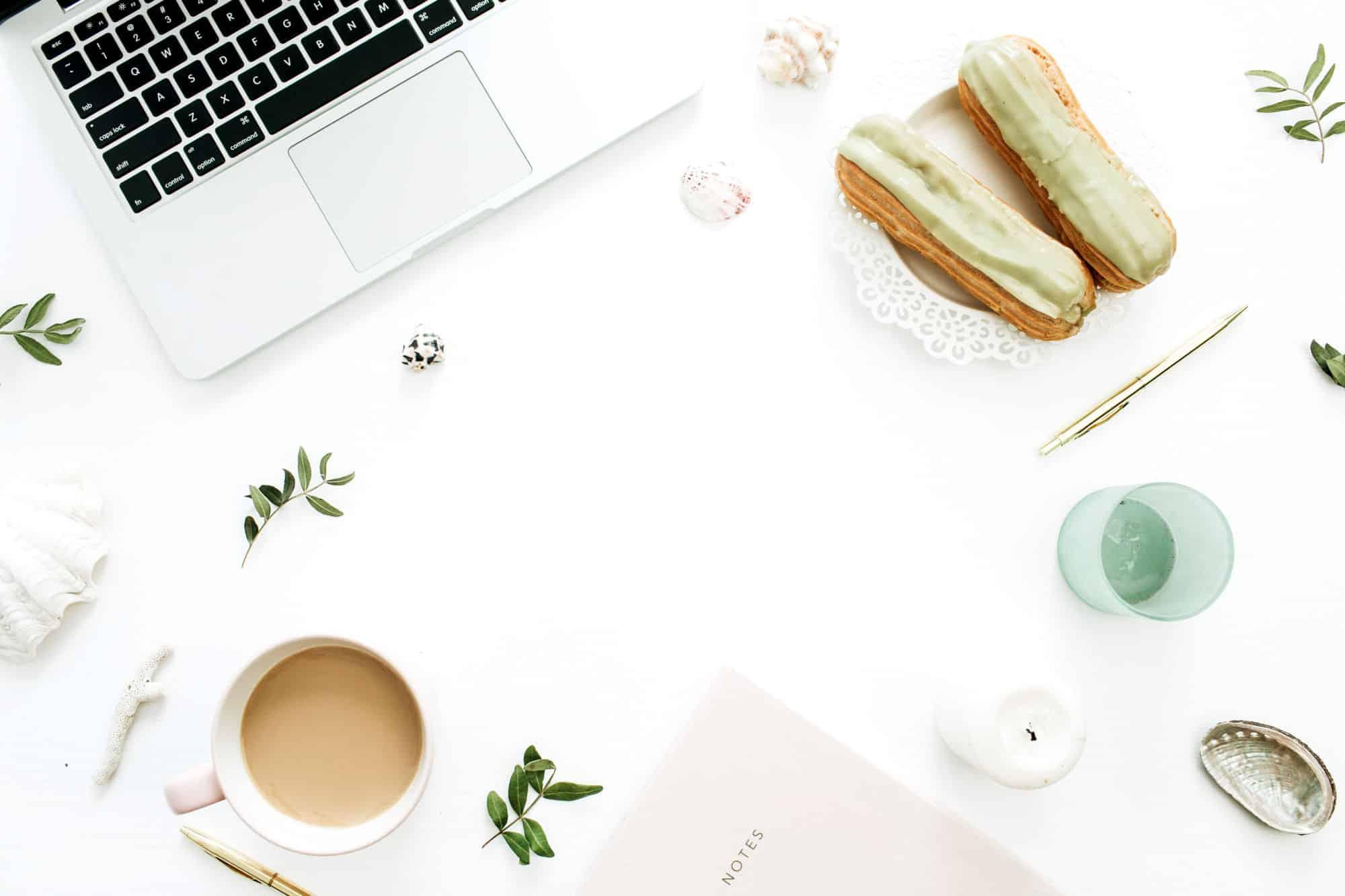Ilustrační foto - pracovní stůl snotebookem, kávou amušlí
