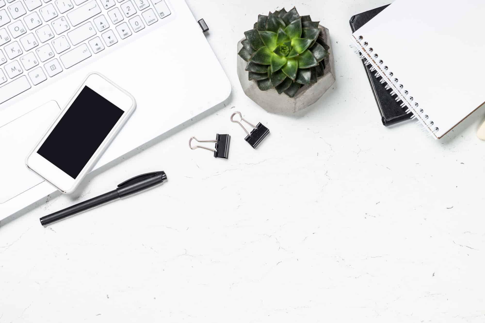 Ilustrační foto - pracovní stůl snotebookem, mobilem azápisníkem